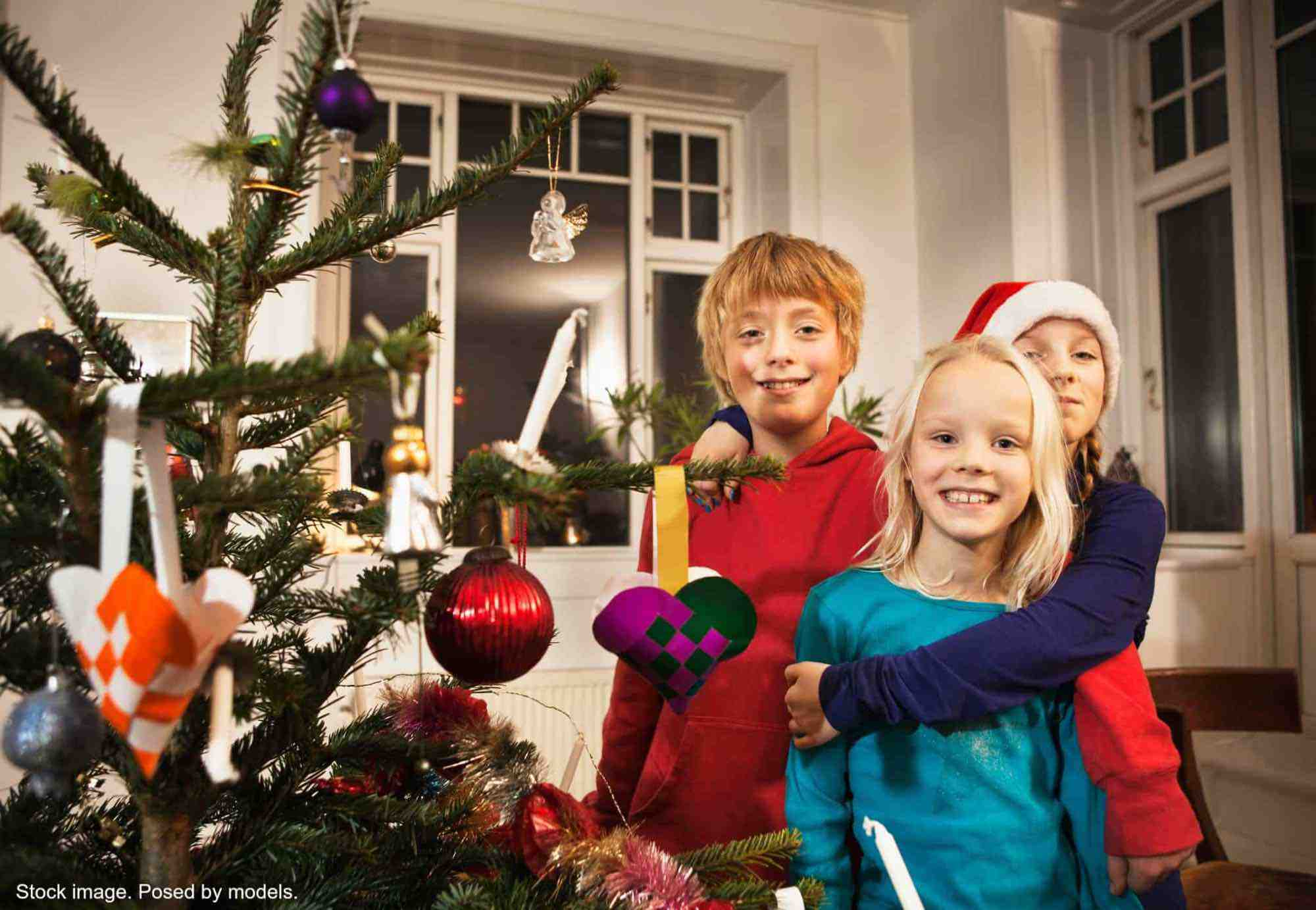 3 smiling kids hugging near the Christmas tree. Stock photo. Posed by models.