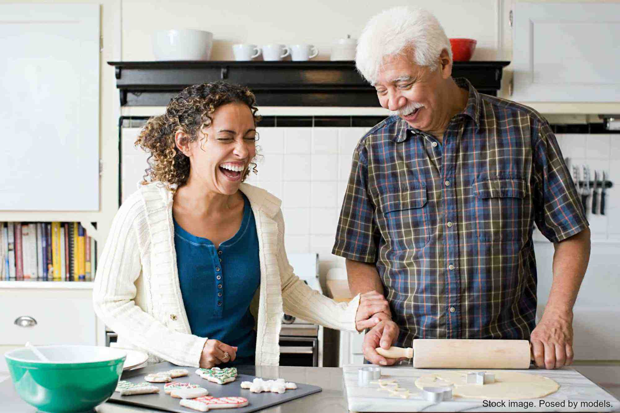 Grown woman and her dad rolling out cookies and laughing. Stock photo. Posed by models.