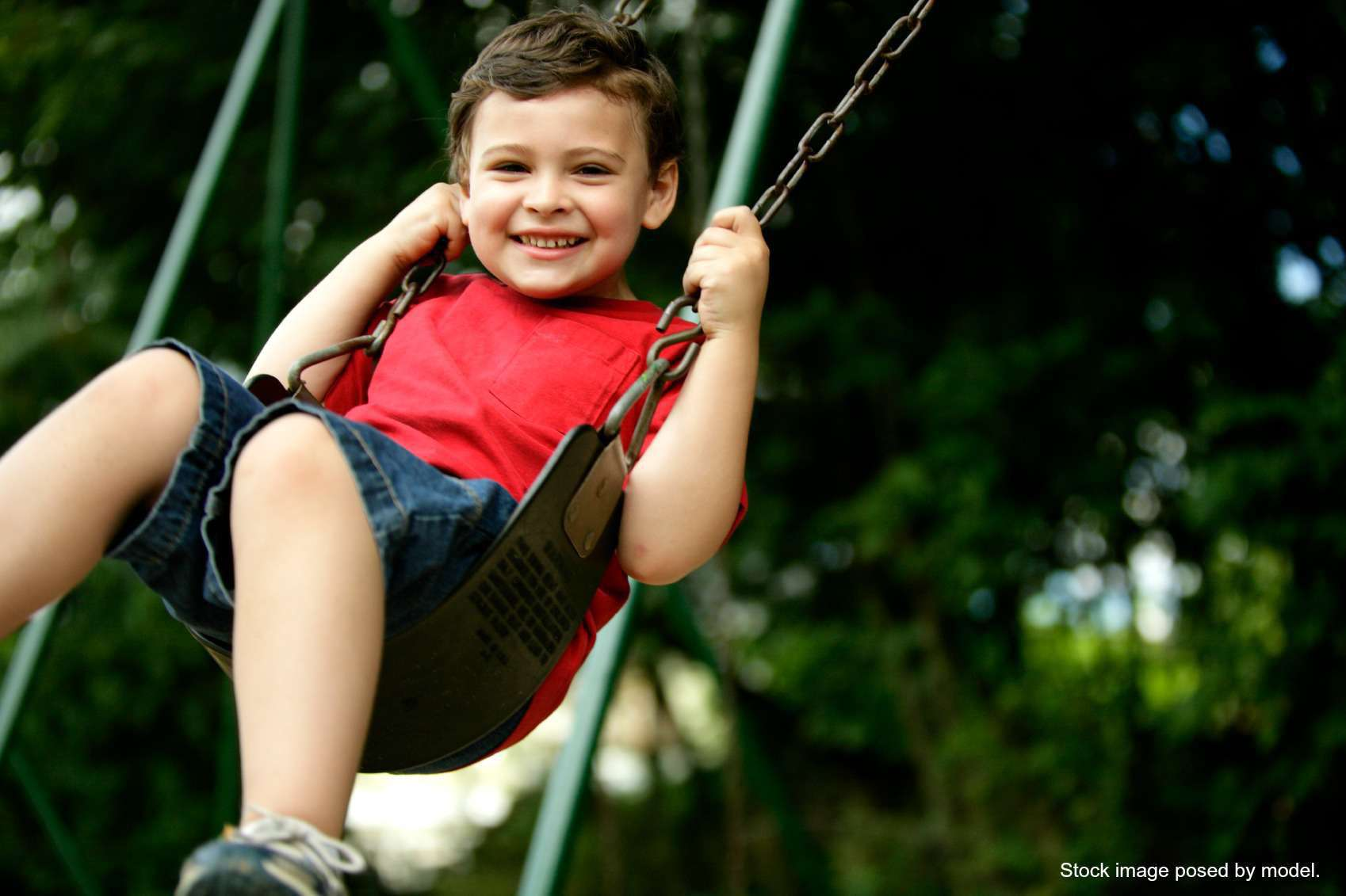 Smiling little boy swinging in the park