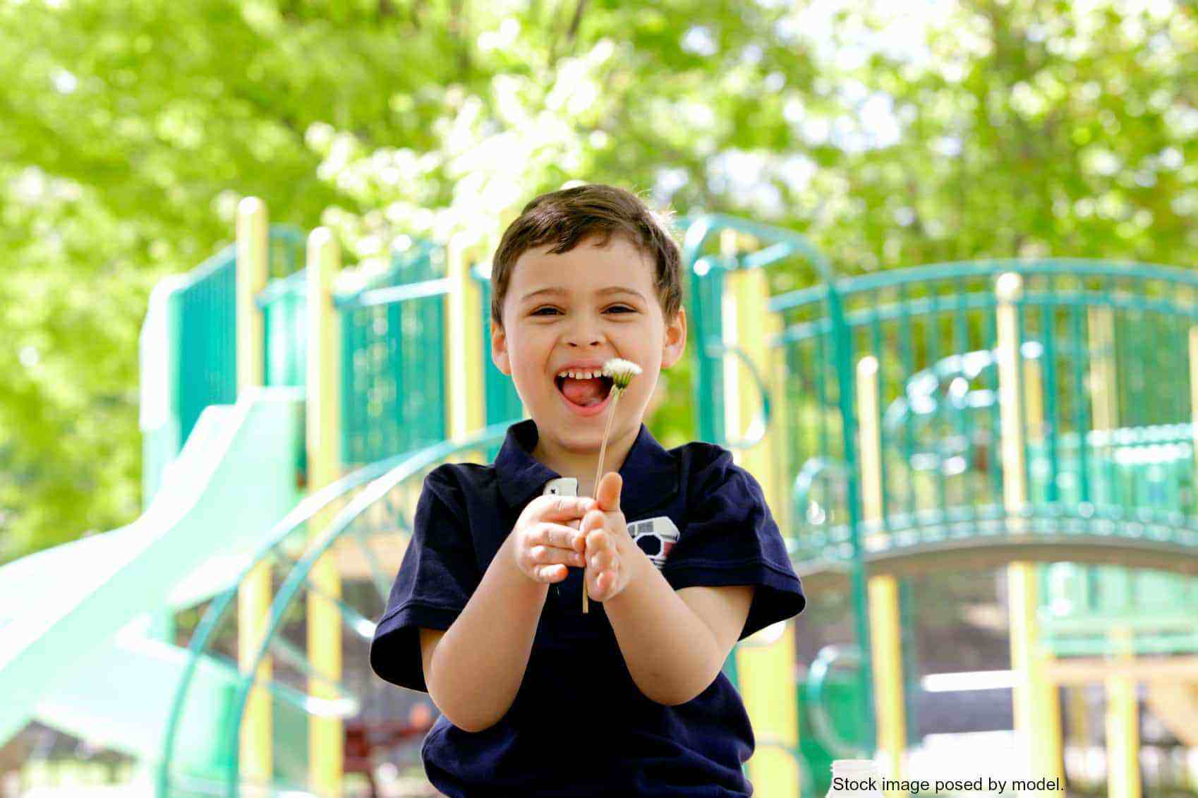 Little boy at playground smiling with dandelion in hands