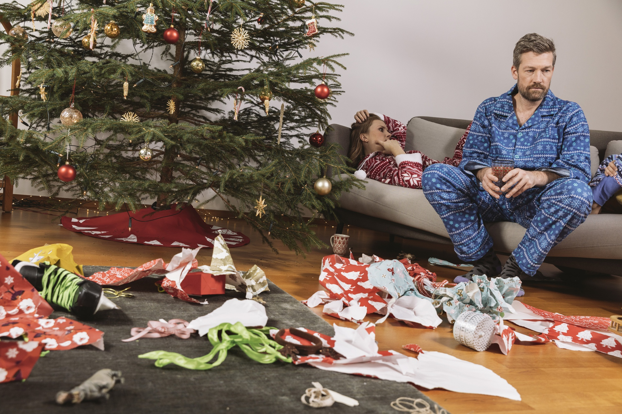 Unhappy man sitting next to unhappy wife on Christmas morning