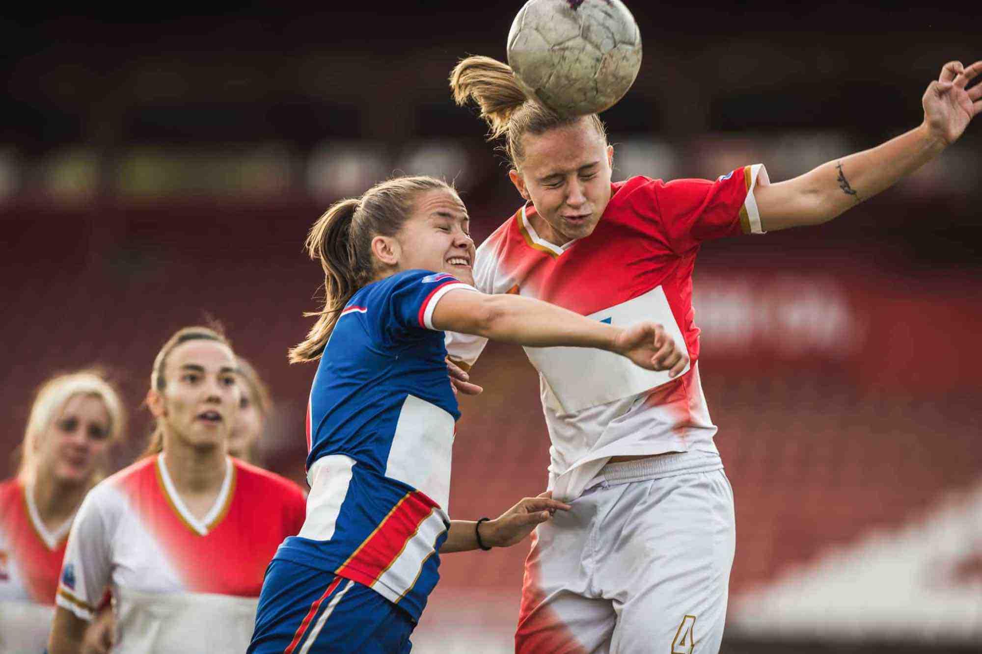 Teen girls soccer game; one girl using head to deflect soccer ball
