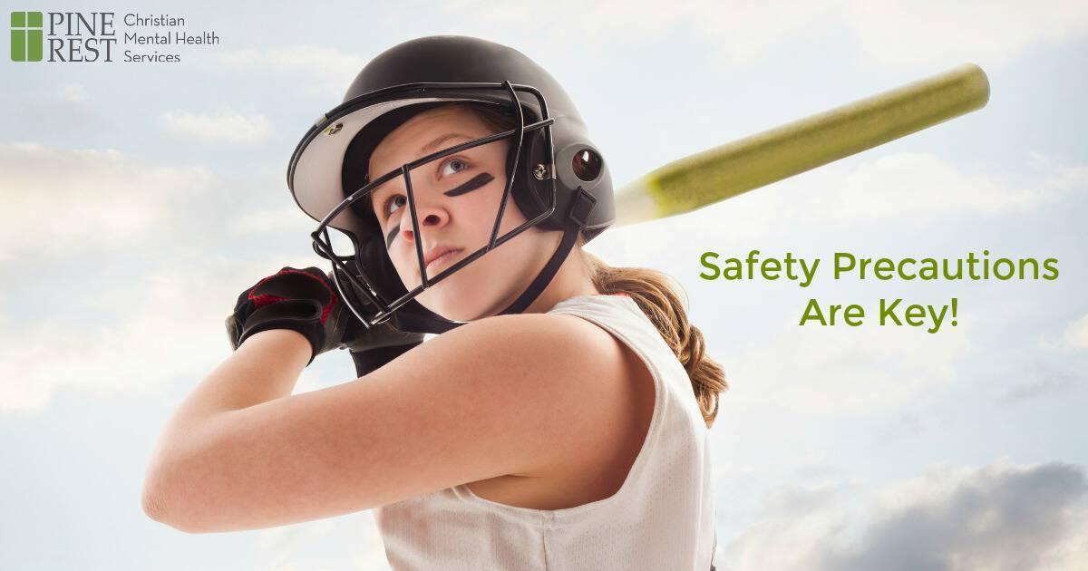 Female softball player wearing helmet and preparing to bat