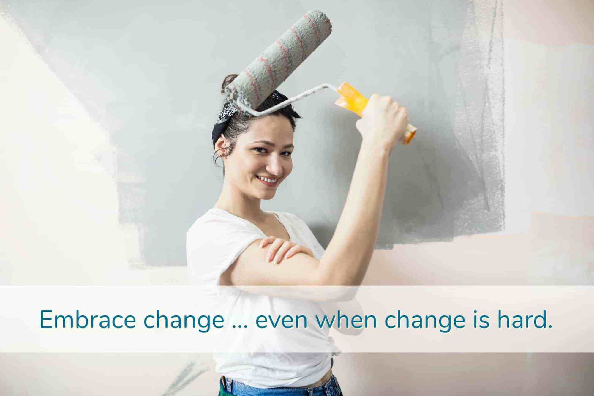 Strong, smiling woman holding up paint roller while flexing bicep