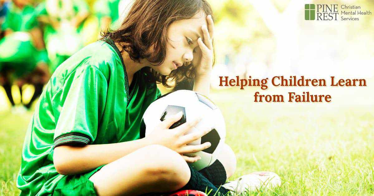 Sad little girl sitting with soccer ball in lap
