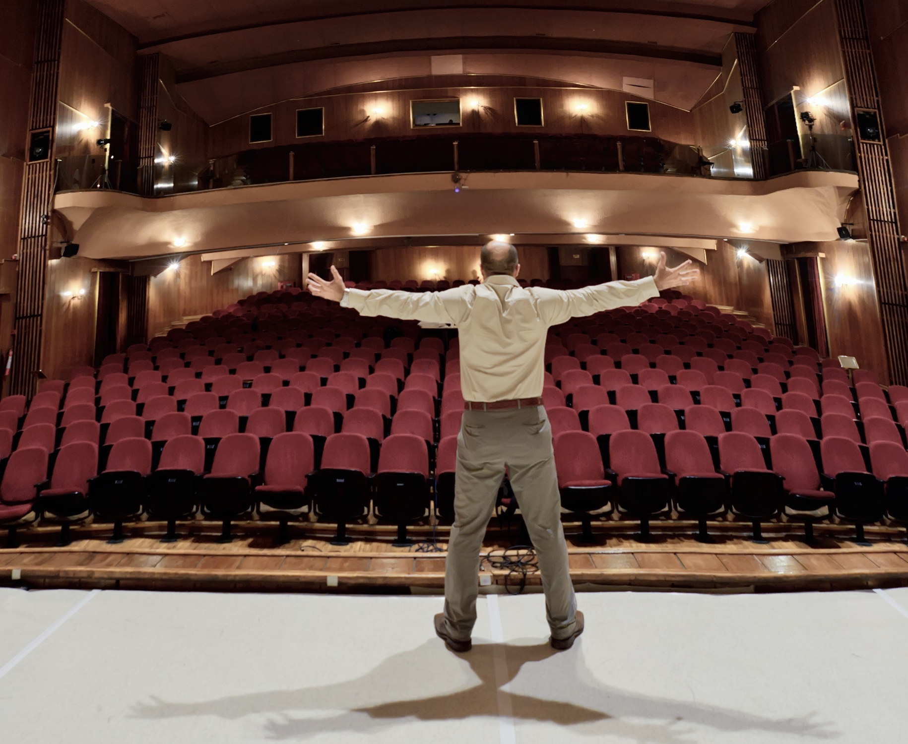 Man rehearsing on stage in front of an empty theater