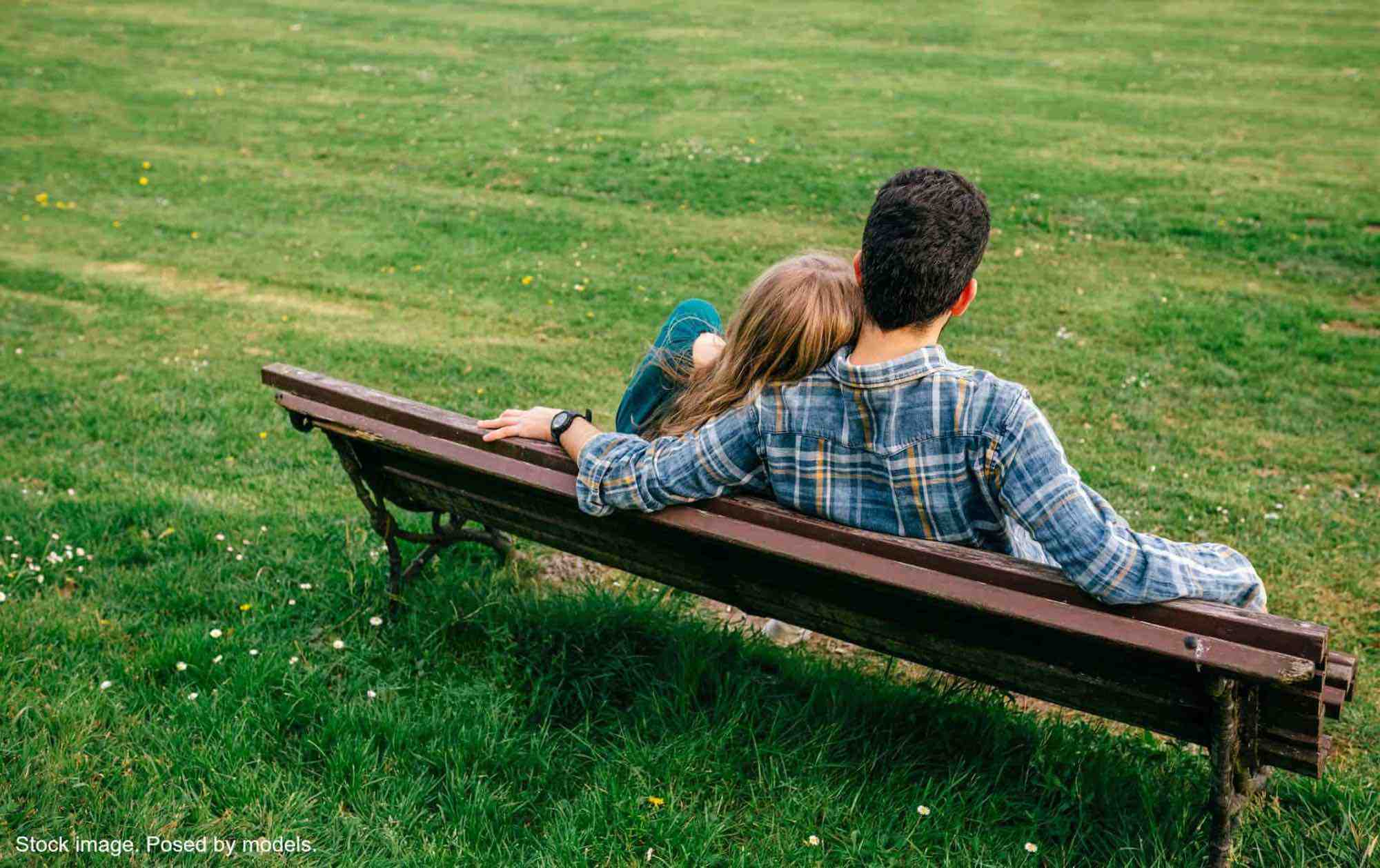 View from the back of couple sitting on a park bench, woman leaning against the man.
