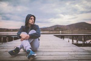 Young man in jeans and a hoddie sitting on a dock, the sky is overcast