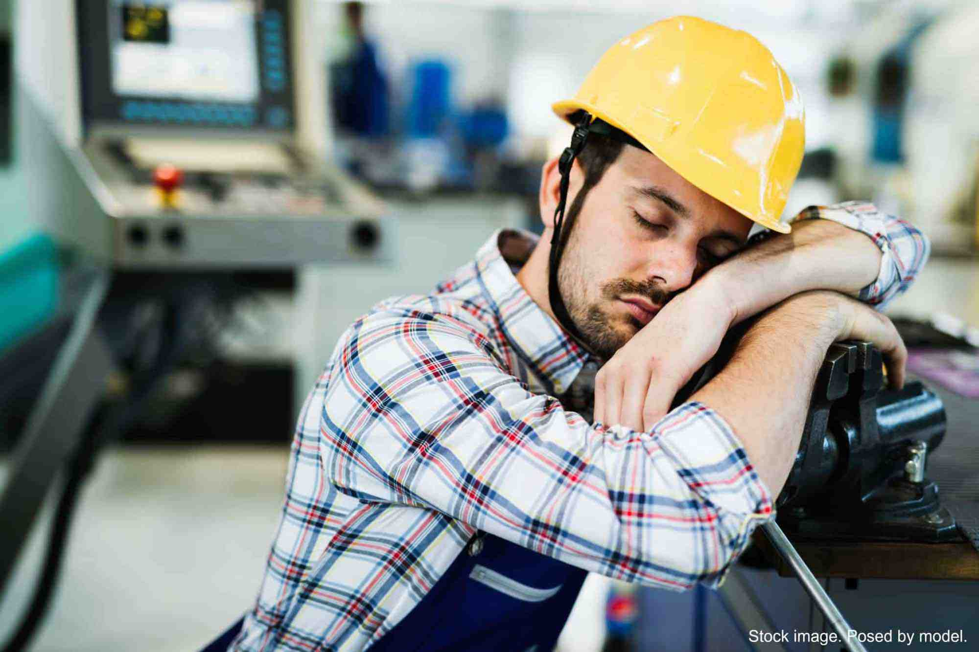 Factory Worker Leaning Against Machine, Eyes Closed
