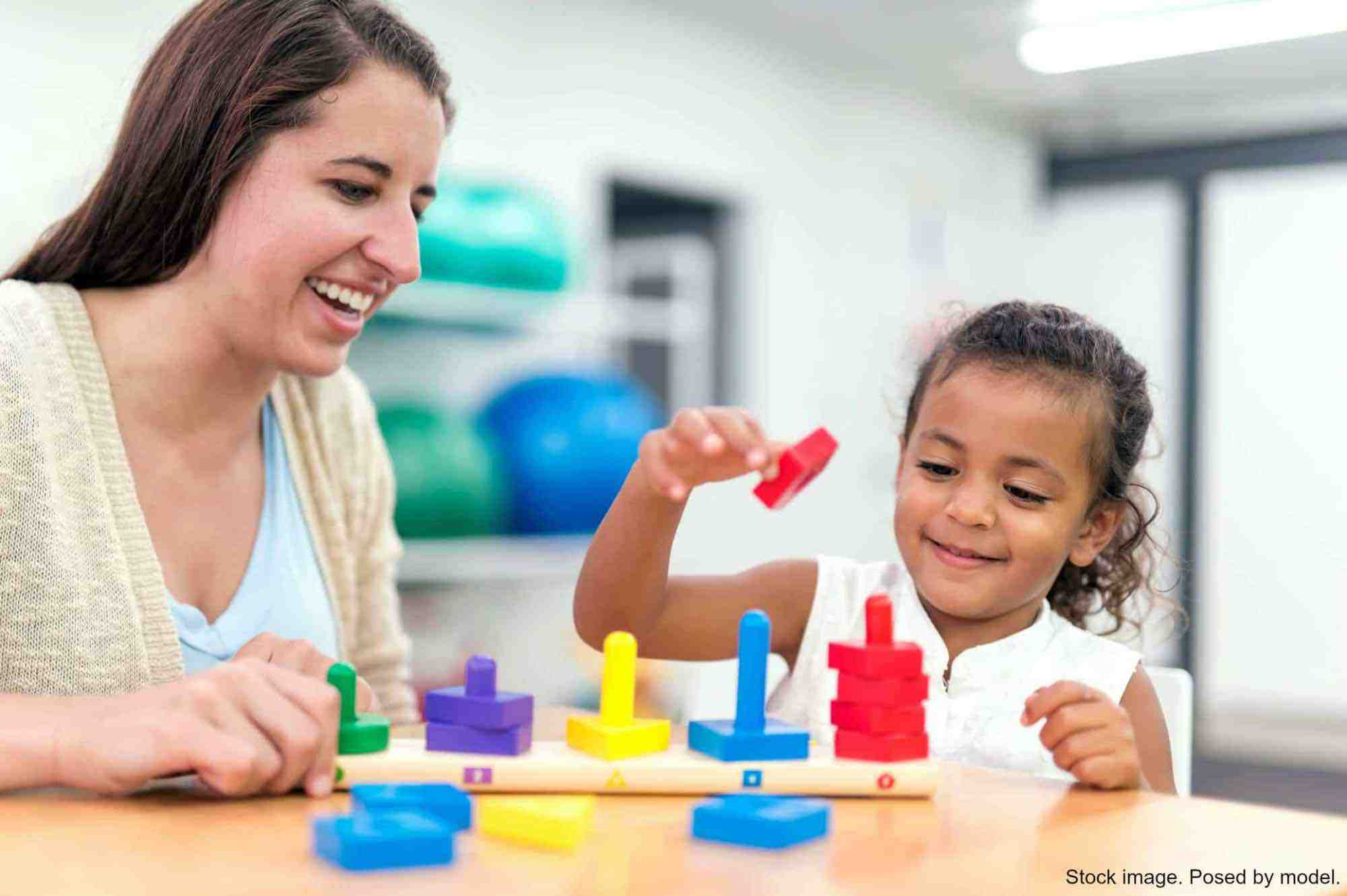 Therapist working with young child on a block puzzle