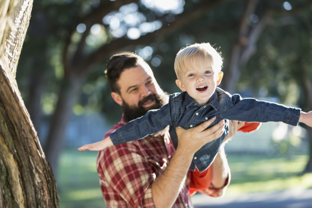 Man with dark hair and full beard holding his small son in the front yard of their home.