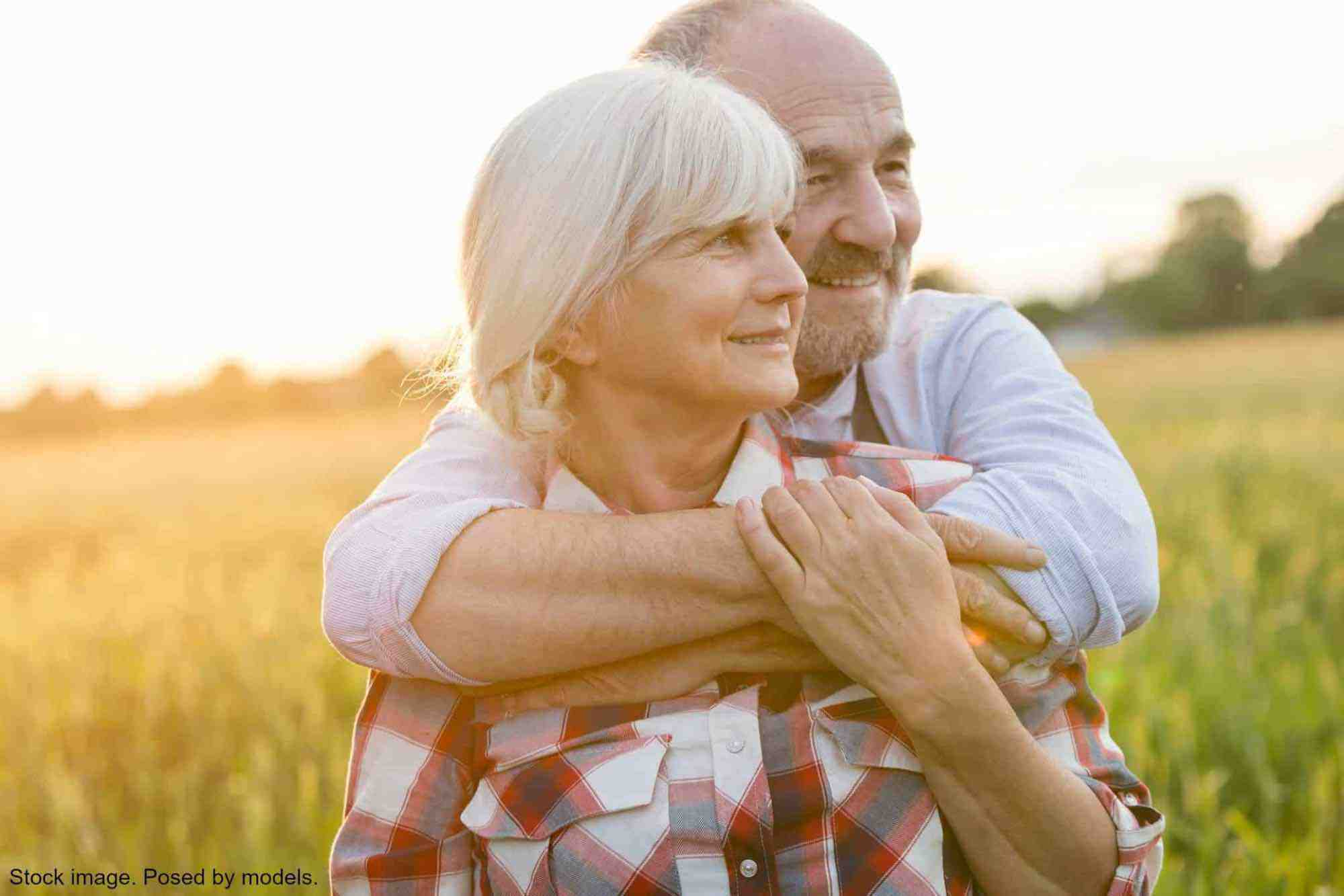 Older couple embracing in field