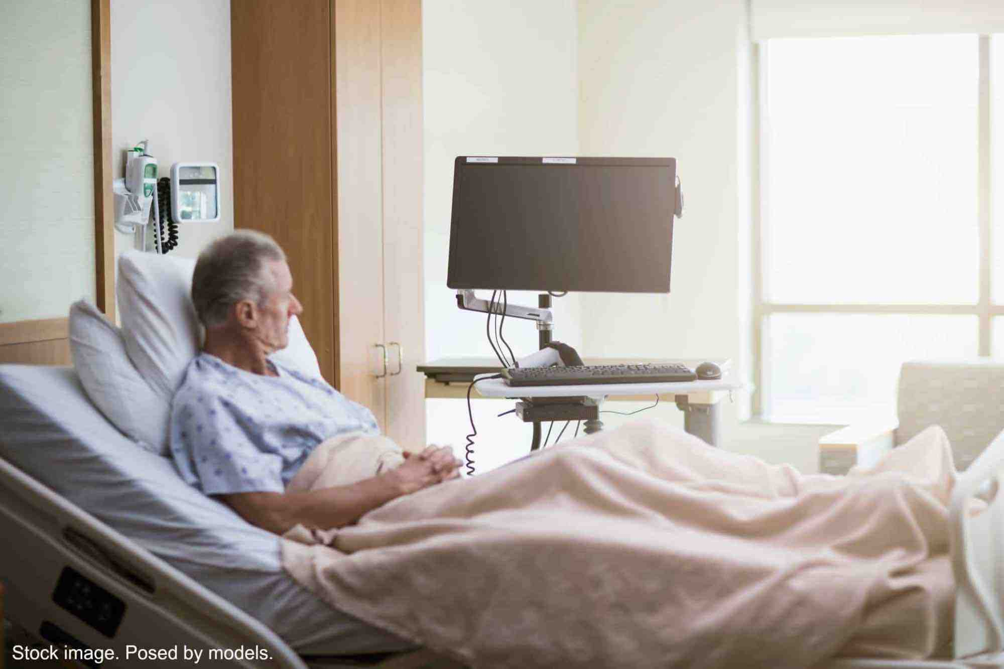Man sitting up in hospital bed, alone