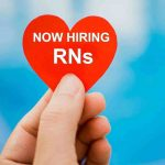 Hand holding up heart printed with the words 'Now hiring RNs'