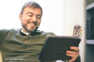 Man sitting on the sofa at home using digital tablet.