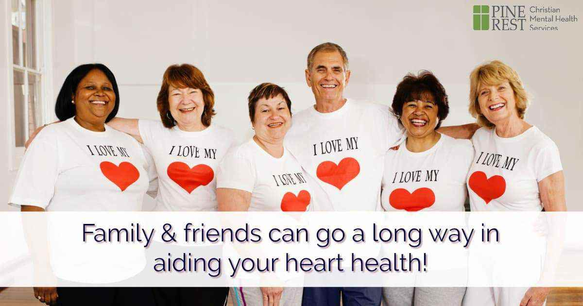 Group of smiling friends lined up, all wearing identical heart t-shirts