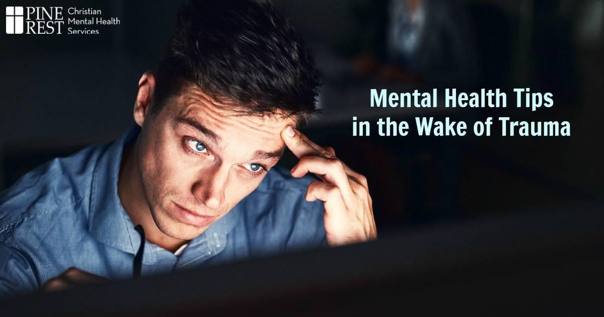 Distressed man looking at computer headlines in the dark