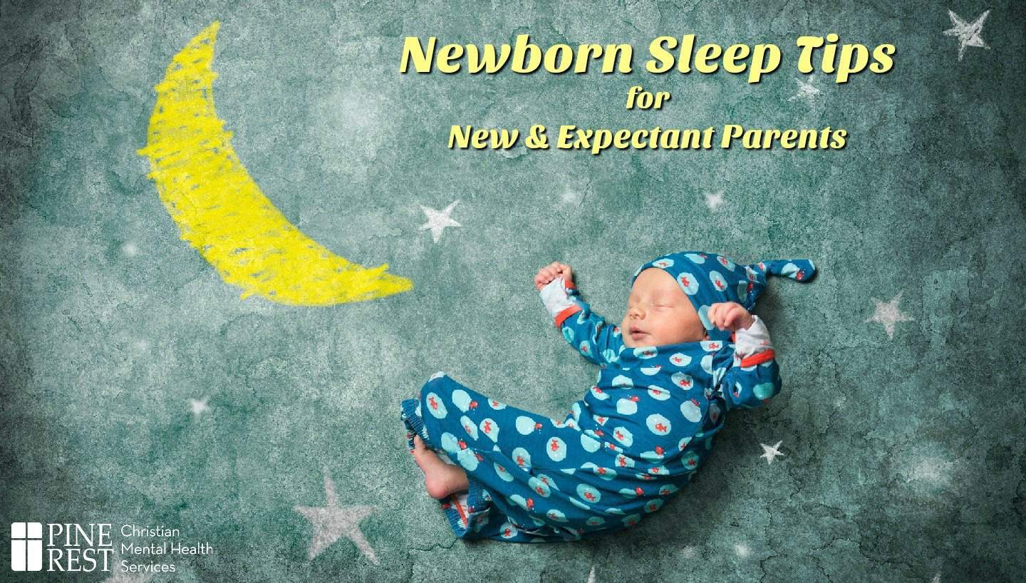 Newborn baby sleeping peacefully next to chalk drawing of moon and stars
