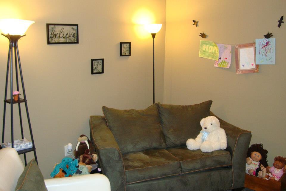 Dolls, stuffed animals and comfortable furniture at play therapist's office