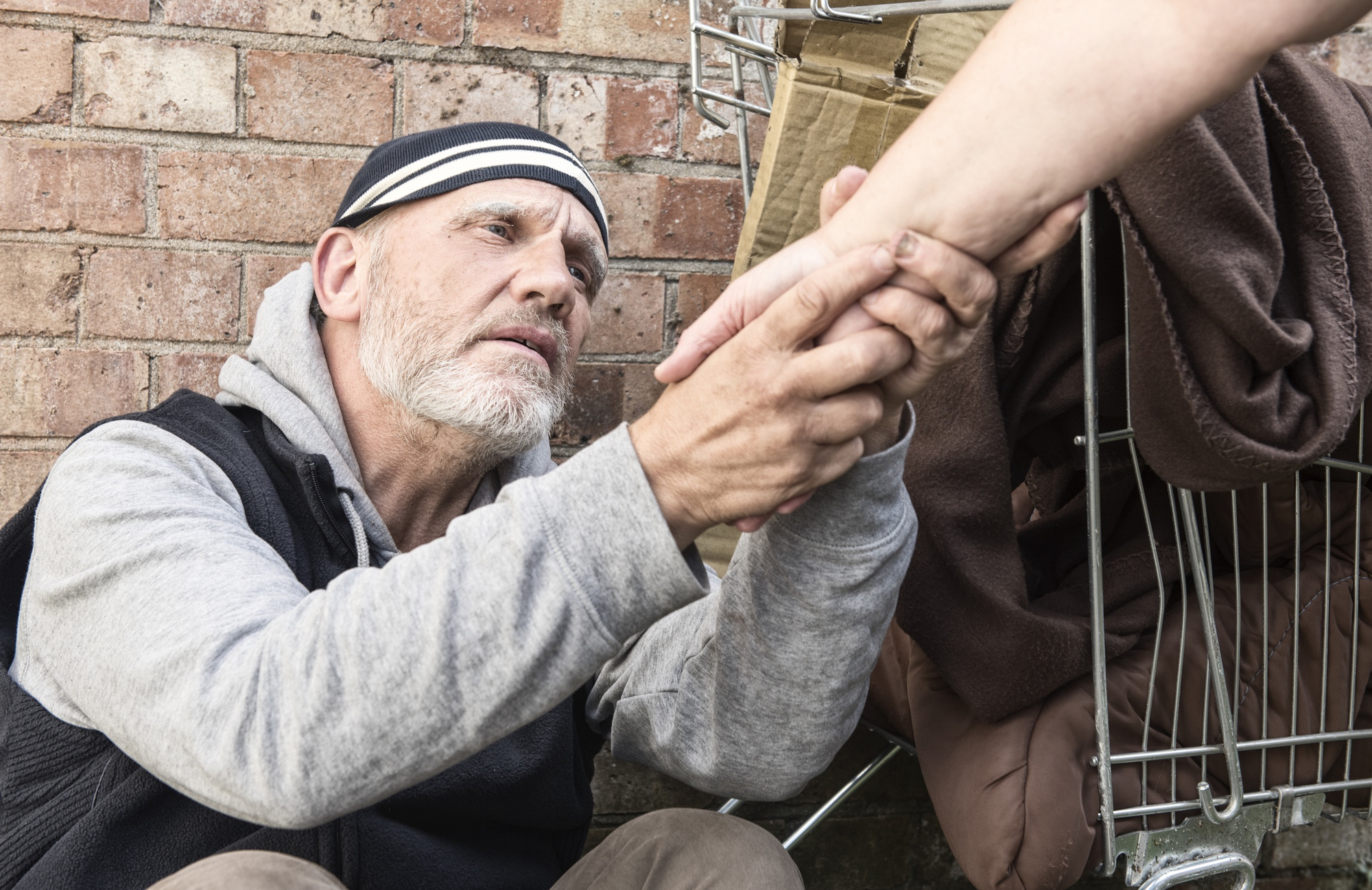 Hand outstretched to help homeless man. Stock photo. Posed by models.