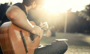 Man strumming guitar outside in the sunlight