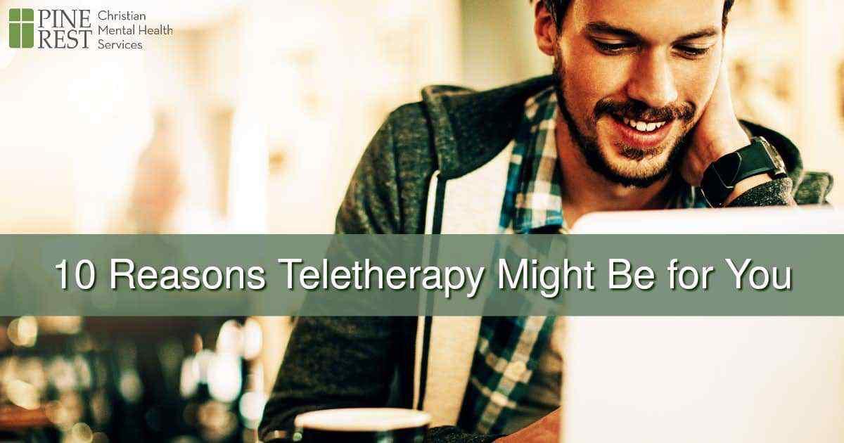 Smiling man on laptop at coffeeshop