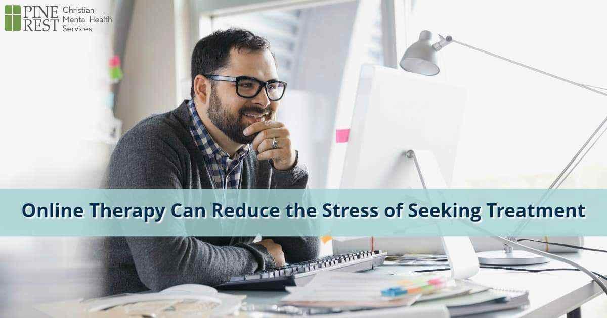 Smiling man sits at laptop computer