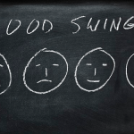 Faces drawn on chalk board with expressions from happy to sad