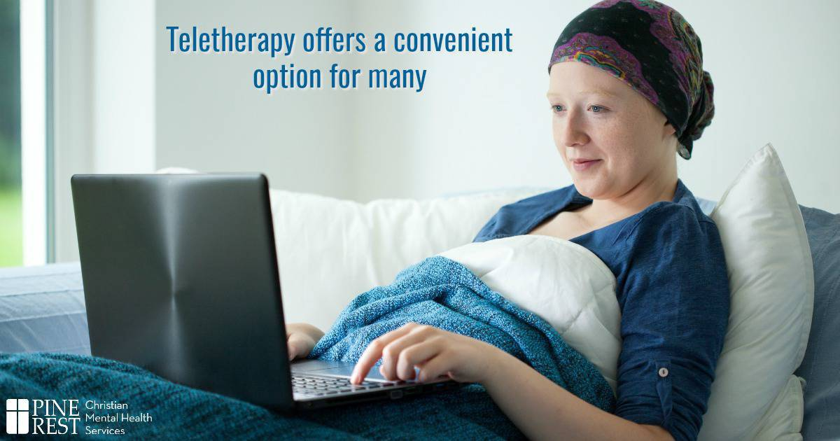Cancer patient sitting up in bed on laptop computer