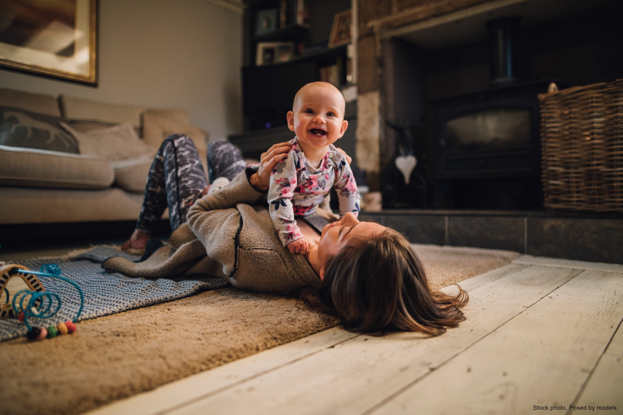 Mother playing with infant on living room floor. Stock photo. Posed by models.