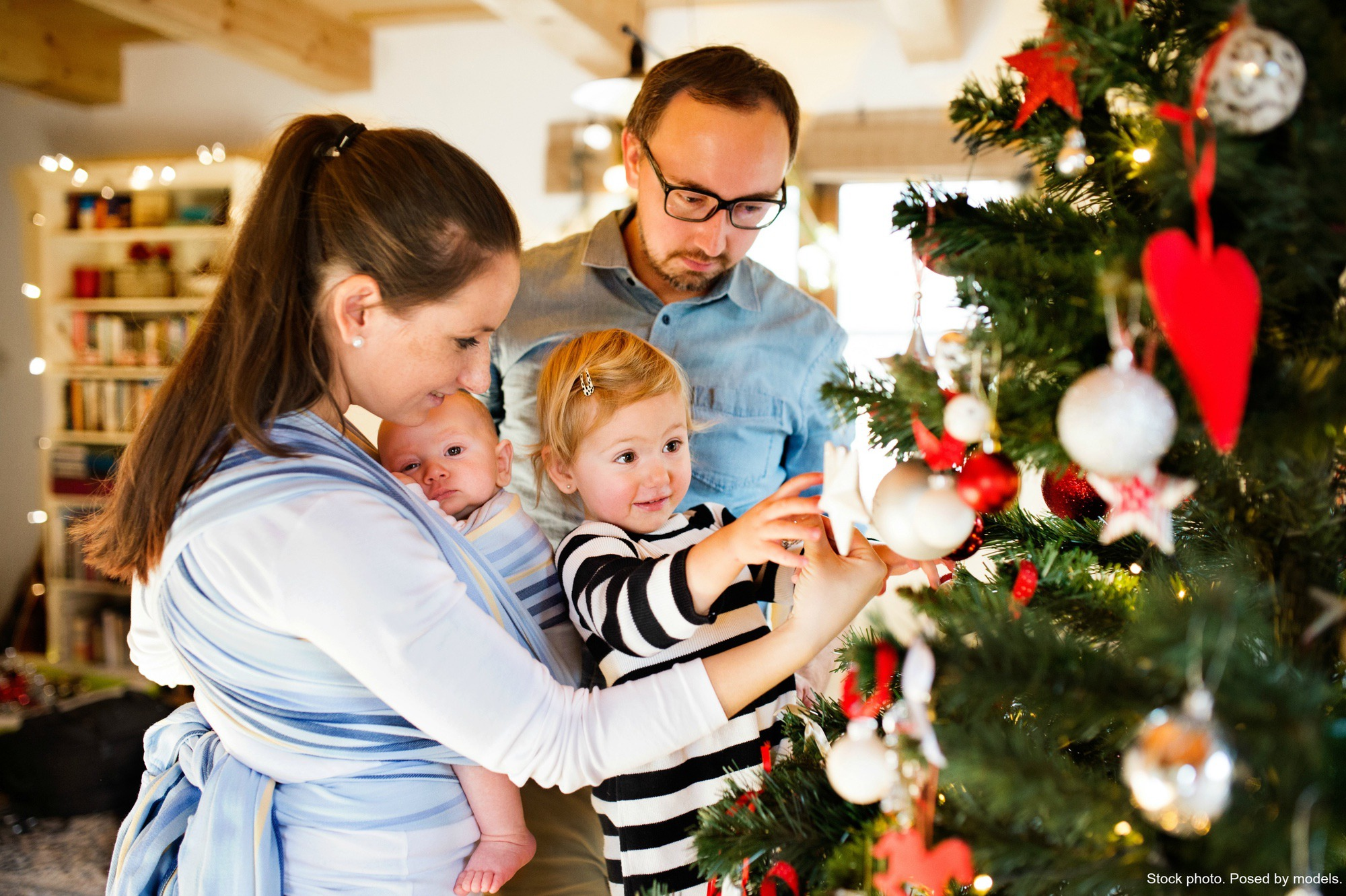 Young family decorating tree. Stock photo. Posed by models