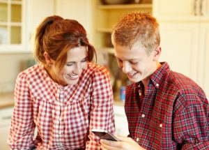 Mother and son looking at a smartphone   Technology: Friend or Foe - Pine Rest Blog