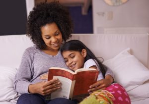 Cropped shot of a young mother reading to her daughter at home